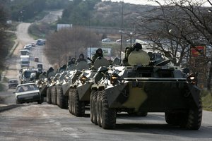 Soldiers, believed to be Russian, ride on military armoured personnel carriers on a road near the Crimean port city of Sevastopol
