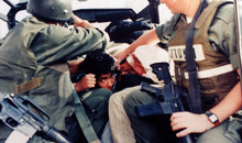 A Palestinian man is arrested by Israeli border police in Jerusalem in October 2000. Two armed police officers have him restrained in the back of a truck
