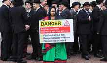 EDITORIAL USE ONLY Protest outside City Hall in Cardiff, ahead of the NATO Summit Wales 2014, Wednesday September 3, 2014 Woman's rights advocate Samira Hamidi, a member of the Afghan Women's Network, from Kabul in Afghanistan, holds a sign whilst surrounded by 39 men to represent that only one in 40 signatories on peace agreements over the last 30 years has been a woman, during an Amnesty International organised protest outside City Hall in Cardiff, ahead of the NATO Summit Wales 2014. The sign reads - Afghan women workers ask the UK to: Find out who I am Keep in touch with me Protect me at work PRESS ASSOCIATION Picture date: Wednesday September 3, 2014. Photo credit should read: Barry Batchelor/PA