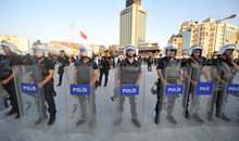 """Turkish riot police surround anti-goverment protestors during a demonstration at Istanbul's Gezi Park on July 28 , 2013. The demonstration was part of """"traveling"""" iftar meals that are being organized in a different public space each evening during the Muslim holy month of Ramadan. Police forces blocked the entry to Istanbul's Gezi Park before cordoning off Taksim Square in an attempt to restrict access to a group that had gathered at the entry of the park. AFP PHOTO / OZAN KOSE (Photo credit should read OZAN KOSE/AFP/Getty Images)"""