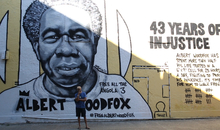 """Robert King, one of the 'Angola 3' stands in front of a mural depicting his friend, Albert Woodfox. The mural in New Orleans, Louisiana, was painted by artist Brandan """"B-Mike"""" Odums in conjunction with Amnesty International USA. Albert Woodfox has spent 40 years in solitary confinement, locked up alone in a tiny cell with little natural light for 23 hours a day. He was convicted in 1973 for the murder of a prison guard the year before, while he was serving time for robbery. But Albert says he is an innocent man. There was no physical evidence linking him to the crime, and his conviction relied primarily on the dubious testimony of another prisoner, who received a pardon in return. Albert believes his conviction was politically motivated because he was a member of the Black Panther Party, the radical black rights movement."""