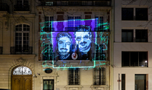 Photograph taken at night showing an image of prisoners of conscience (2 in 13 : Farida Ghulam, Ebrahim Sharif) onto the Bahrain Embassy in France, an Amnesty International France action during the 2013 Write for Rights events.