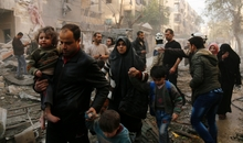 TOPSHOT - Syrians make their way through debris as they leave for a safer place following air strikes in the rebel-controlled side of the northern city of Aleppo on January 13, 2016. On January 12, 2016, suspected Russian strikes killed 57 civilians, including children and paramedics, in Idlib province, adjacent to Latakia, and in Aleppo, Syrian Observatory for Human Rights said. / AFP / KARAM AL-MASRI (Photo credit should read KARAM AL-MASRI/AFP/Getty Images)
