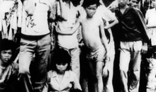 Black and white photograph shows men, women and children, families from Vietnam on boats as they arrive in Hong Kong. At the end of the war in Viet Nam and the years following it, many Vietnamese people felt the need to flee the country for reasons of personal safety. In the summer of 1979 a conference was held in Geneva where it was decided Hong Kong, would be one of the countries to offer first asylum, meaning the refugees would be admitted and allowed to remain until they were permanently resettled outside the region. On 2 July 1982 the Hong Kong Government changed its policy and began detaining all Vietnamese refugees in closed detention centres. The government's stated purpose in introducing this policy was solely to discourage further arrivals from Vietnam.