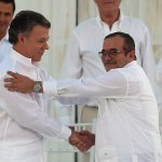 Colombia's President Juan Manuel Santos, left, and the top commander of the Revolutionary Armed Forces of Colombia (FARC) Rodrigo Londono, known by the alias Timochenko, shake hands after signing a peace agreement between Colombia's government and the FARC to end over 50 years of conflict in Cartagena, Colombia, Monday, Sept. 26, 2016. (