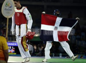 Luisito Pie of the Dominican Republic, right, celebrates with his national flag after defeating Jesus Tortosa Cabrera of Spain compete in a men's Taekwondo bronze medal final at the 2016 Summer Olympics in Rio de Janeiro, Brazil, Wednesday, Aug. 17, 2016.