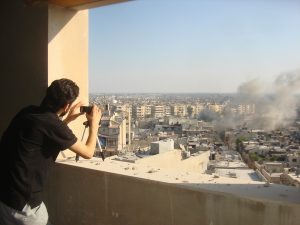 An activist takes a photo of smoke rising from Juret al-Shayah in Homs July 24, 2012.