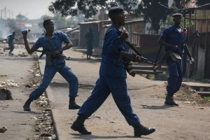 epa04773743 A Burundian police officer throws a teargas canister at protesters during an anti-government demonstration against President Pierre Nkurunziza's bid for a third term in Cibitoke neighborhood of Bujumbura, Burundi, 29 May 2015. Three cars parked outside a bank in downtown Bujumbura exploded on 29 May, injuring at least one person, according to an eye witness. The cause of explosion is unclear. Protesters against the President continued their daily demonstrations as police officers fired shots in an attempt to disperse them. Burundi's Catholic church said on 28 May that it will not support upcoming elections and asked priests serving for electoral commissions to step down, according to media reports. Burundi is scheduled to hold parliamentary and Presidential elections on 05 June and 26 June respectively amid waves of deadly street protests against President's bid for a third term. EPA/DAI KUROKAWA