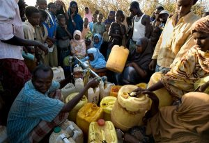 Somali refugees wait for water, Dadaab, Kenya, December 2008. The three camps at Dadaab, which were designed for 90,000 people, now have a population of about 250,000 Somali civilians, making it one of the world's largest and most congested refugee sites. Resources, such as food and water, have been stretched dangerously thin in the overcrowded camps, with sometimes 400 families sharing one tap. There is no room to erect additional tents and the new arrivals are forced to share already crowded shelters with other refugees.